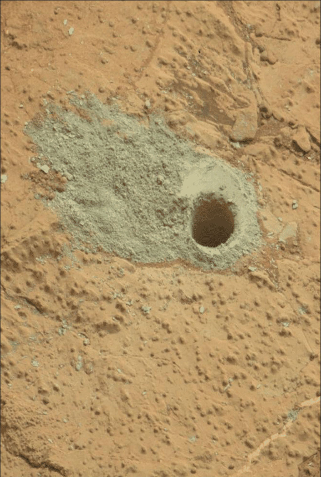 "This image from the Mars Hand Lens Imager (MAHLI) on NASA's Mars rover Curiosity shows the rock target ""Cumberland"" before and after Curiosity drilled into it to collect a sample for analysis."