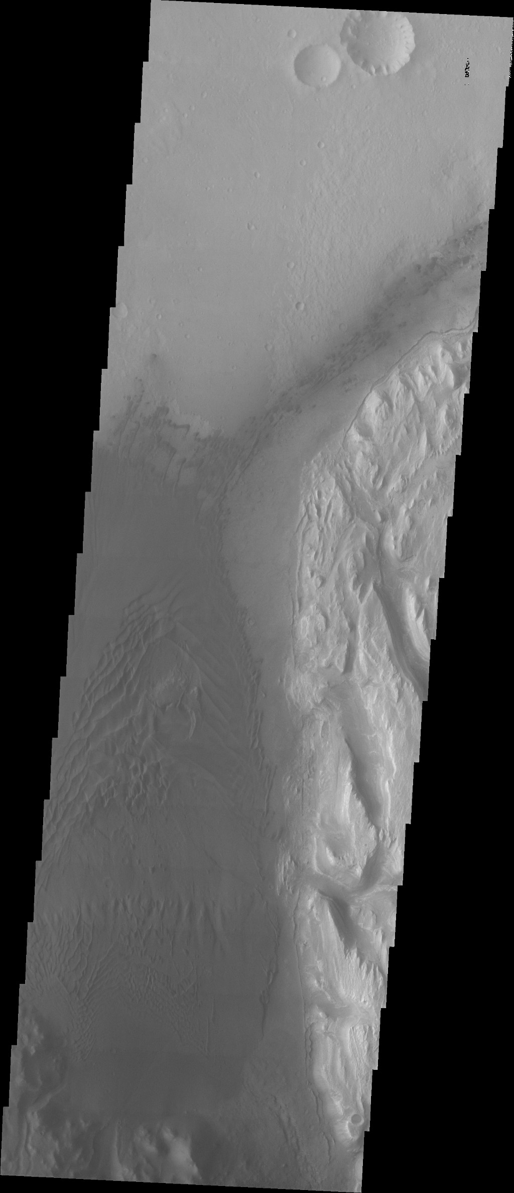 Showing the area just slightly west of the previous image, the large region of sand and sand dunes are the dark area that dominates this image captured by NASA's 2001 Mars Odyssey spacecraft.