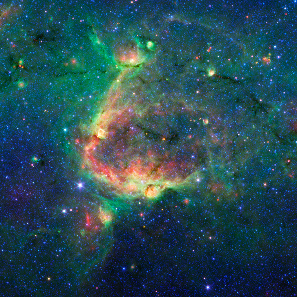 This infrared image from NASA's Spitzer Space Telescope shows a striking example of what is called a hierarchical bubble structure, in which one giant bubble, carved into the dust of space by massive stars, has triggered the formation of smaller bubbles.