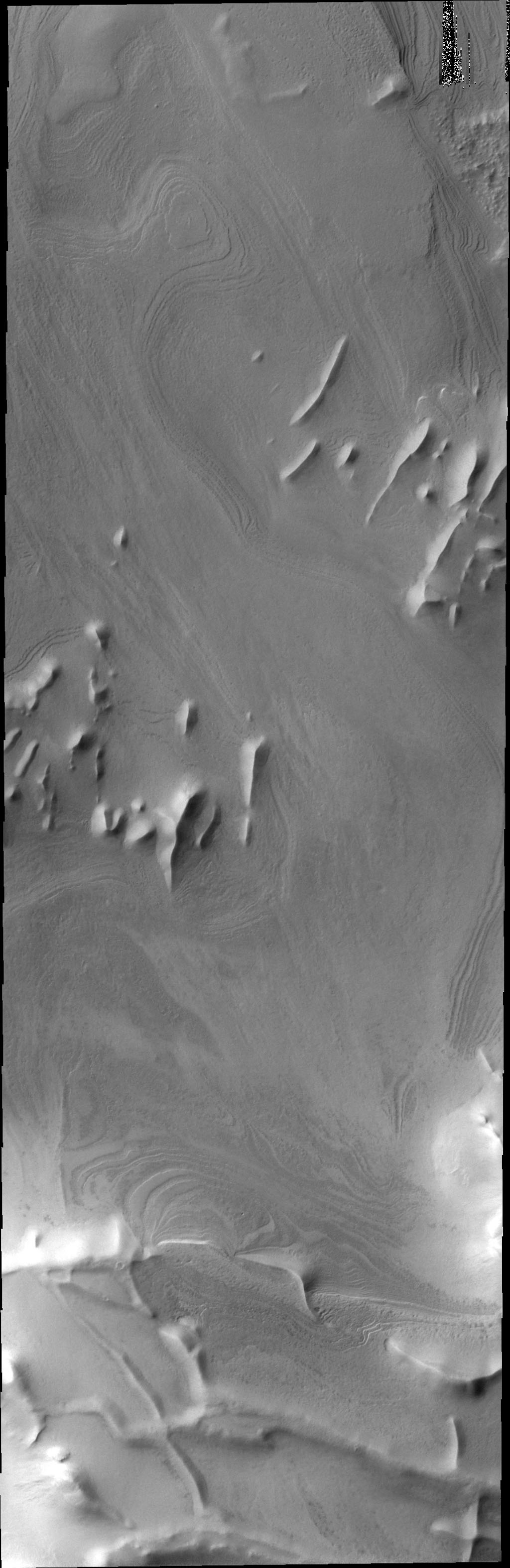 Located further north than yesterday's image, ridges are still prevalent in this image captured by NASA's 2001 Mars Odyssey spacecraft. Layers of material cover this region.