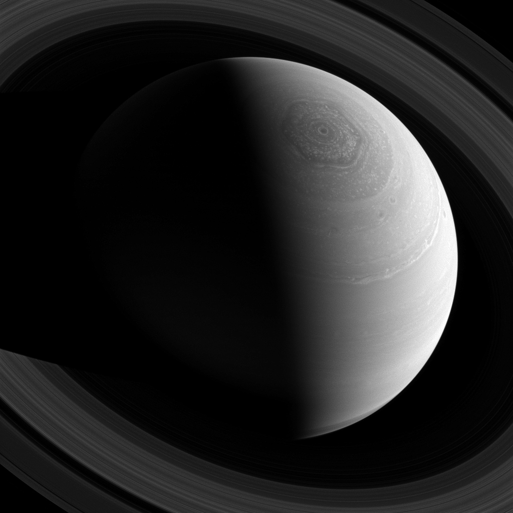 Just as Saturn's famous hexagonal shaped jet stream encircles the planet's north pole, the rings encircle the planet, as seen from NASA's Cassini spacecraft's position high above.