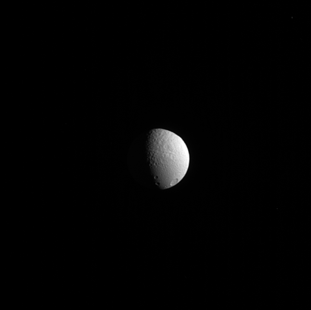 Tethys' trailing side shows two terrains that tell a story of a rough past. To the north (up, in image) is older, rougher terrain, while to the south is new material dubbed 'smooth plains' by scientists. This image was taken by NASA's Cassini spacecraft.