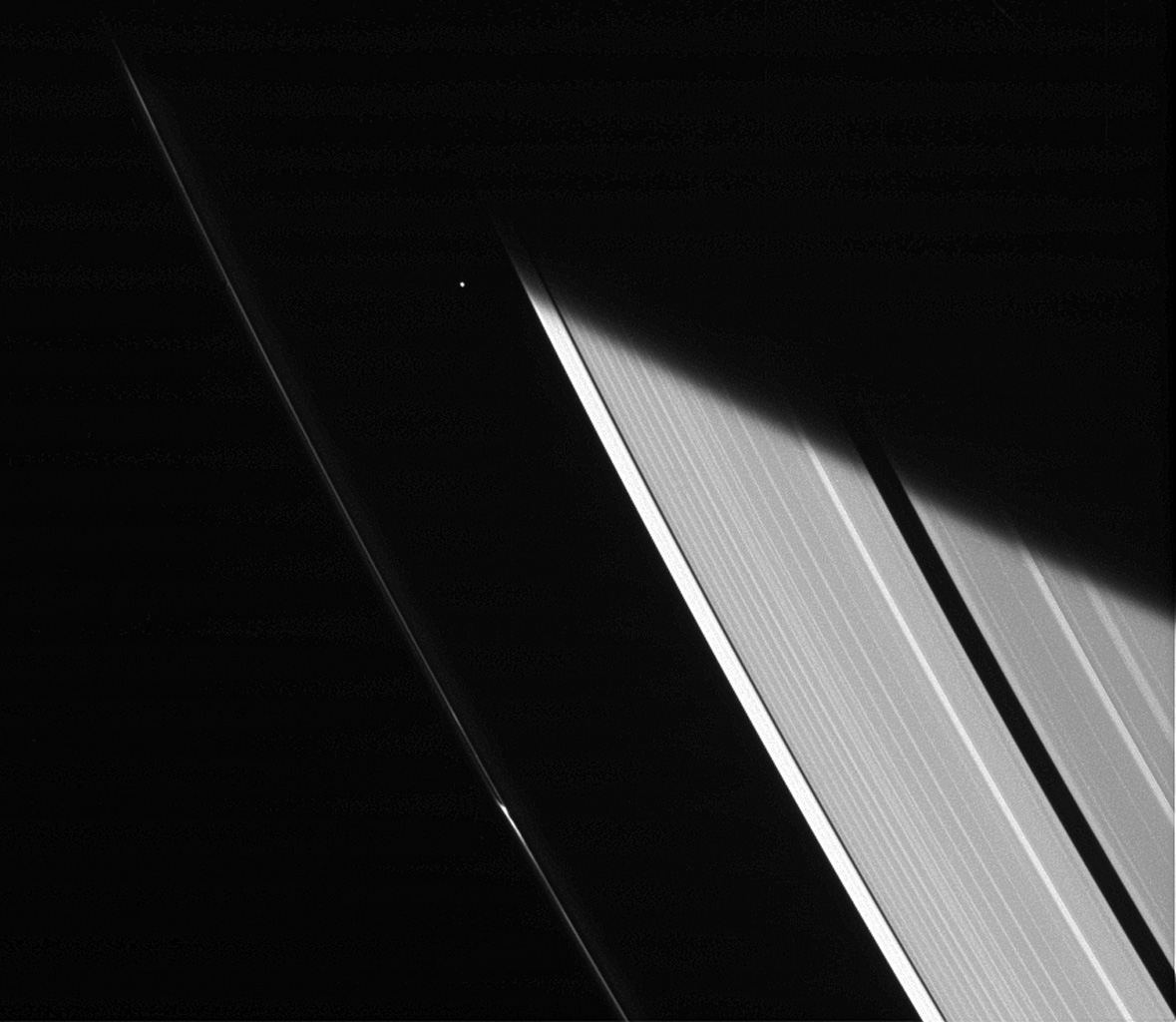 NASA's Cassini spacecraft captures a glimpse of the moon Atlas shortly after emerging from Saturn's shadow.