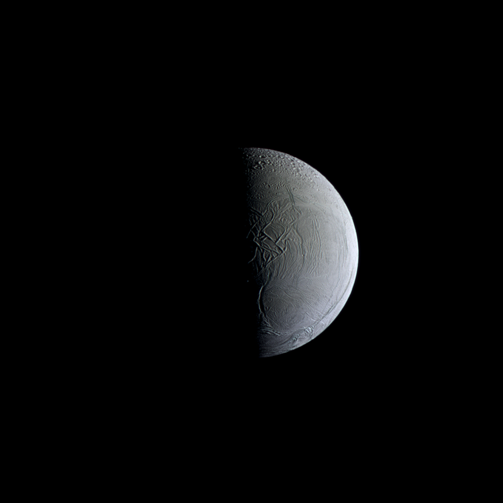 NASA's Cassini spacecraft captures a still and partially sunlit Enceladus. The Saturnian moon is covered in ice that reflects sunlight similar to freshly fallen snow, making Enceladus one of the most reflective objects in the solar system.