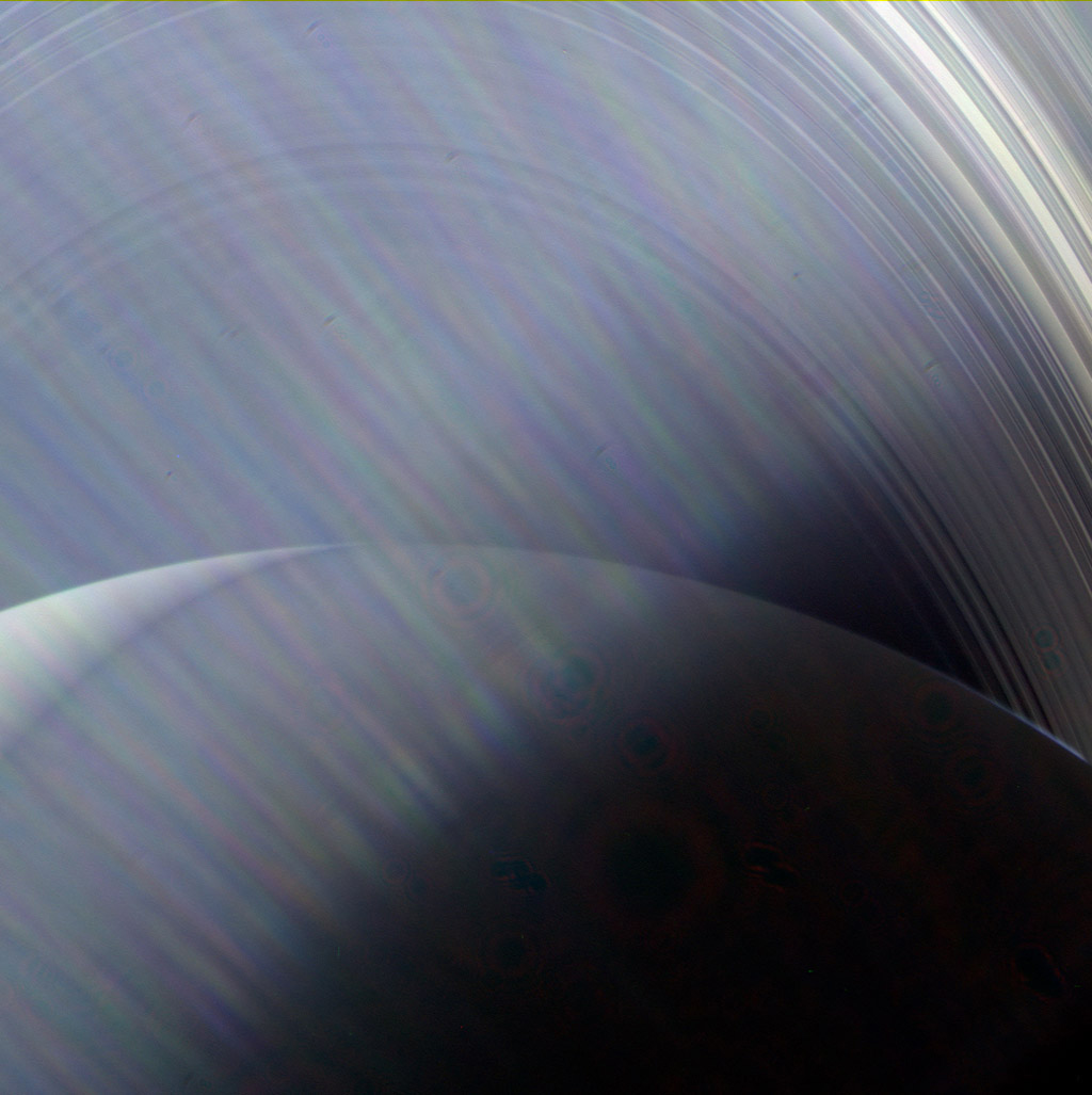 In this image, NASA's Cassini spacecraft sees Saturn and its rings through a wispy haze of Sun glare.