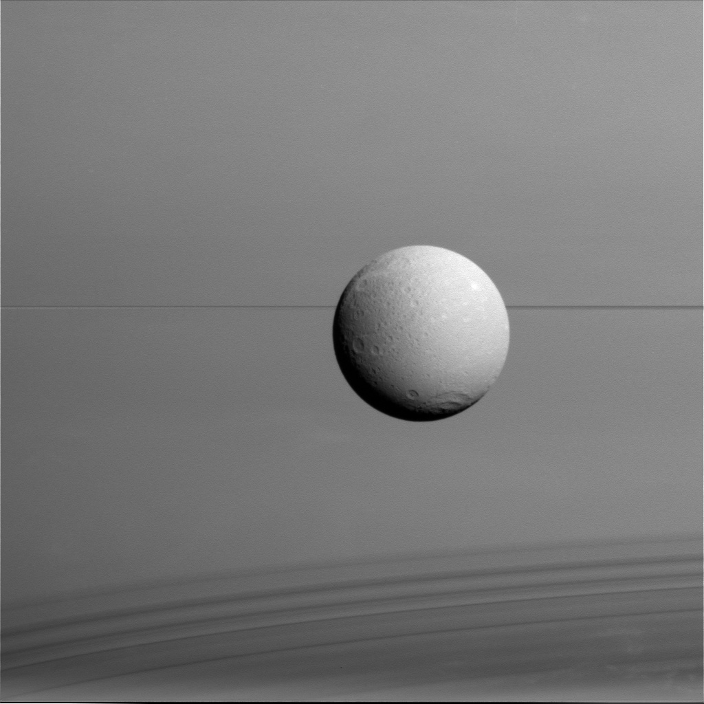 Dione hangs in front of Saturn and its icy rings in this view, captured during Cassini's final close flyby of the icy moon. North on Dione is up.