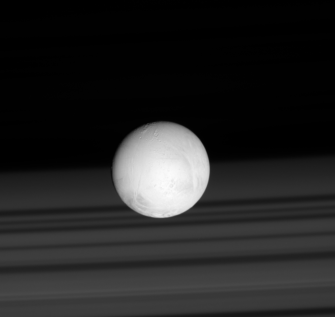 Saturn's rings cast shadows on the planet's cloud tops, providing a perfect backdrop for the brilliant sphere of Saturn's moon Enceladus in this image captured by NASA's Cassini spacecraft.