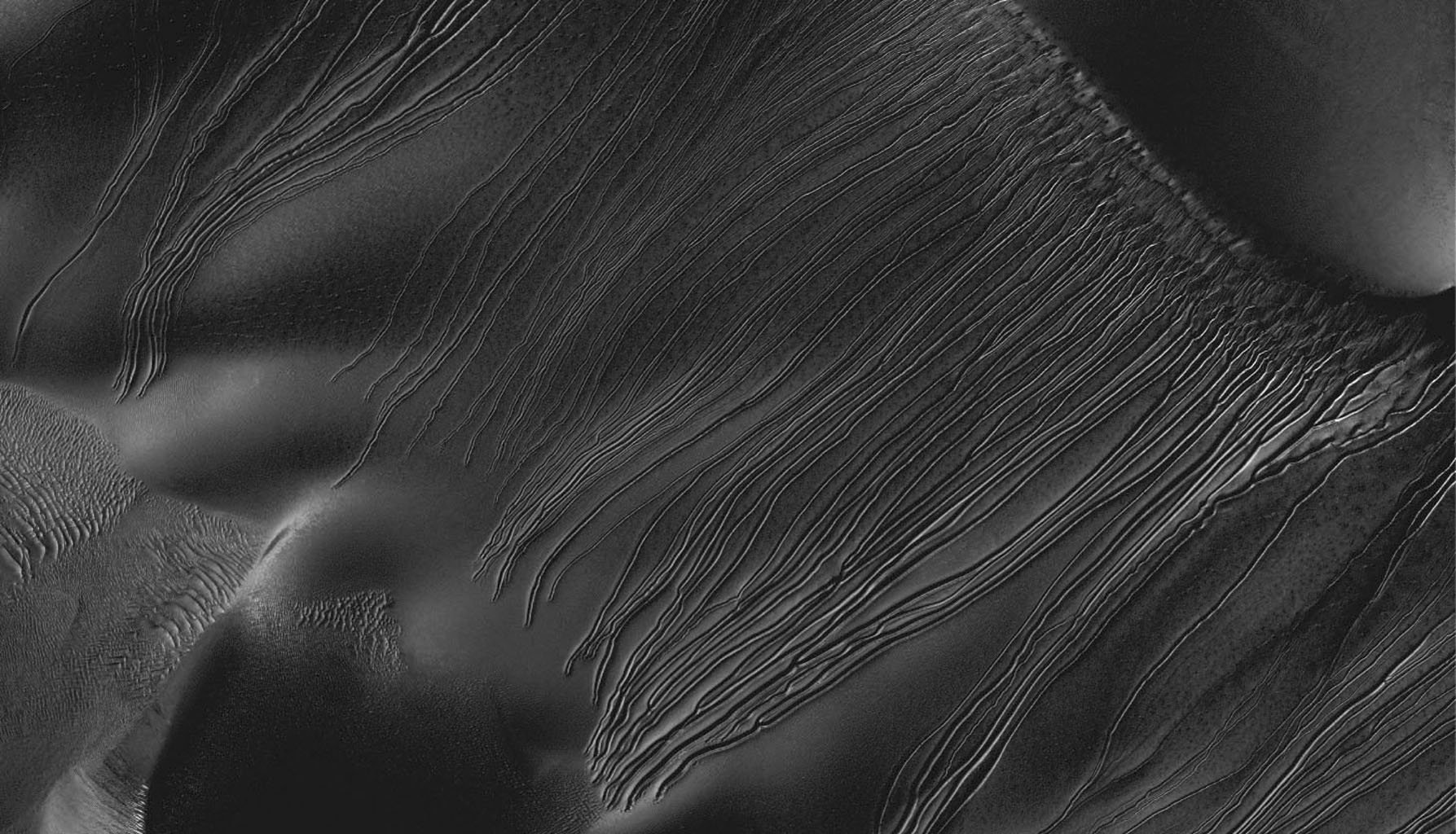 Several types of downhill flow features have been observed on Mars. Shown here is an example of a type called 'linear gullies' as seen by NASA's Mars Reconnaissance Orbiter.