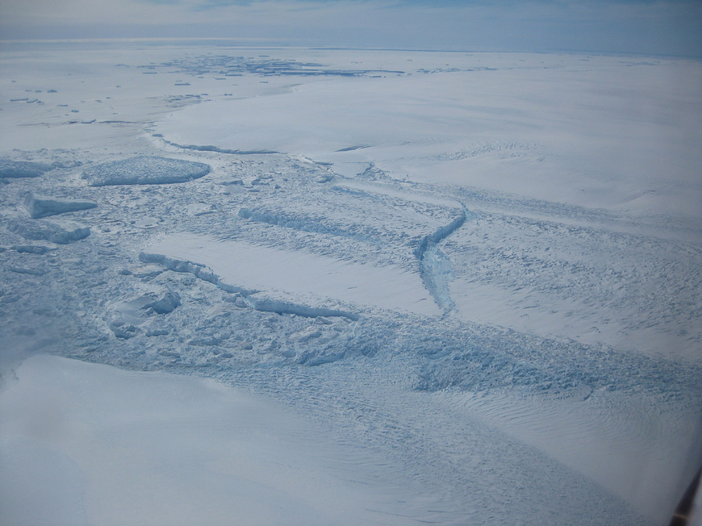This photo, aken onboard a National Science Foundation/NASA chartered Twin Otter aircraft, shows the ice front of Dibble Ice Shelf, East Antarctica, a significant melt water producer from the Wilkes Land region, East Antarctica.