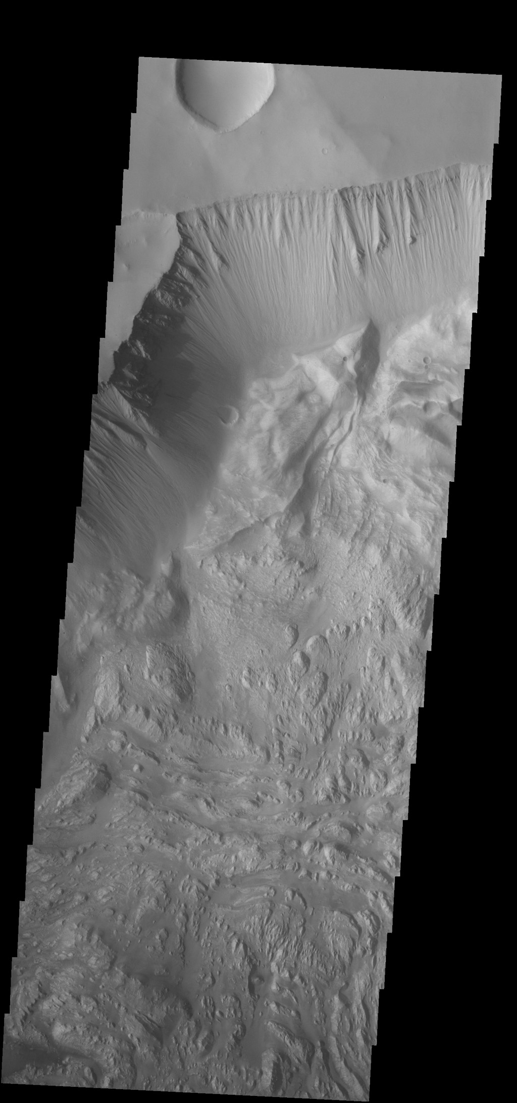 This image from NASA's 2001 Mars Odyssey spacecraft shows part of the wall of Hebes Chasma as well as the complex floor materials.