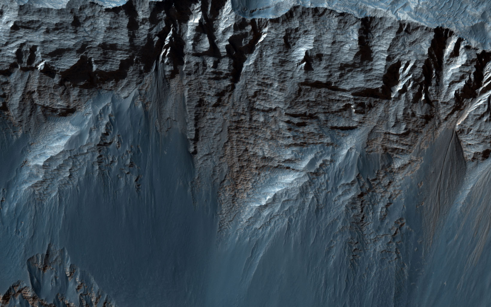 This beautiful image shows terrific layers and exposed bedrock along a cliff in west Candor Chasma, which is part of the extensive Valles Marineris canyon system as seen by NASA's Mars Reconnaissance Orbiter.