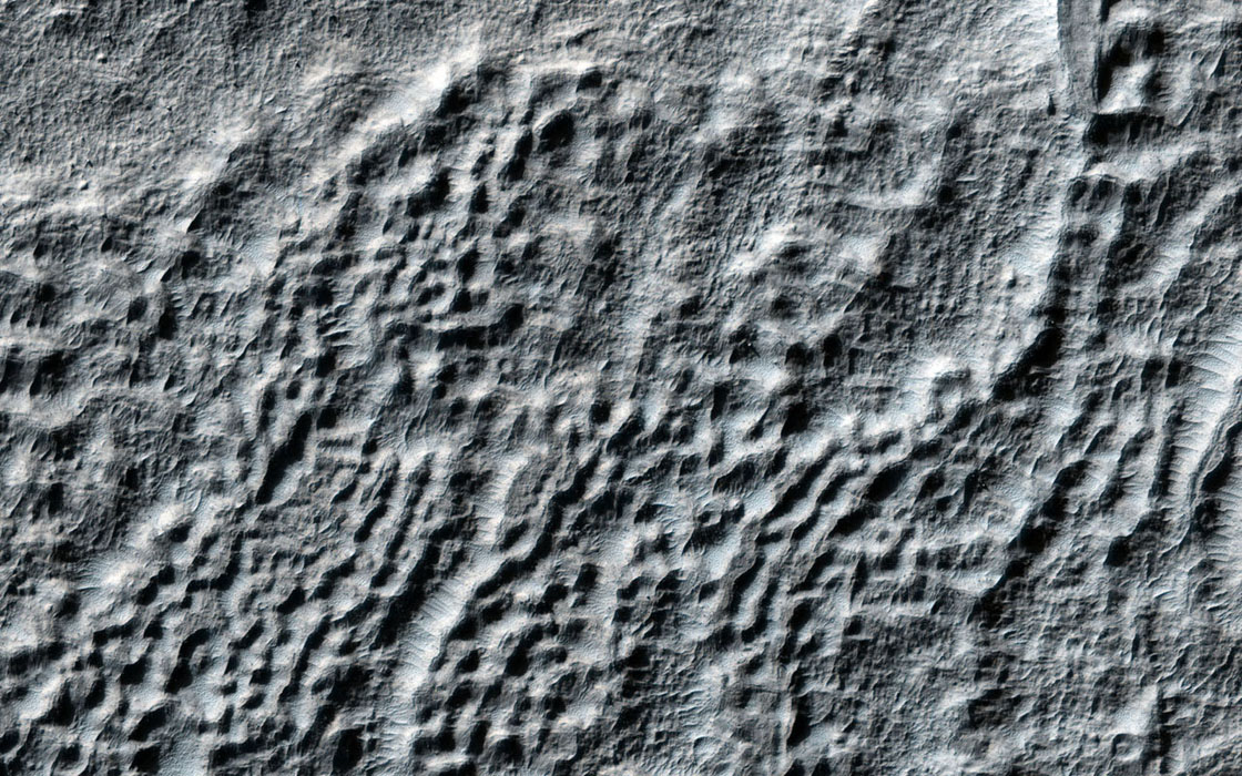 This observation from NASA's Mars Reconnaissance Orbiter shows an excellent example of what is called 'fretted terrain,' termed so because of the eroded appearance of the surface.