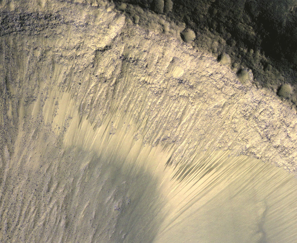 These images from NASA's Mars Reconnaissance Orbiter show how the appearance of dark markings on Martian slope changes with the seasons. The marks, called recurrent slope linea extend down slopes during warmer months.