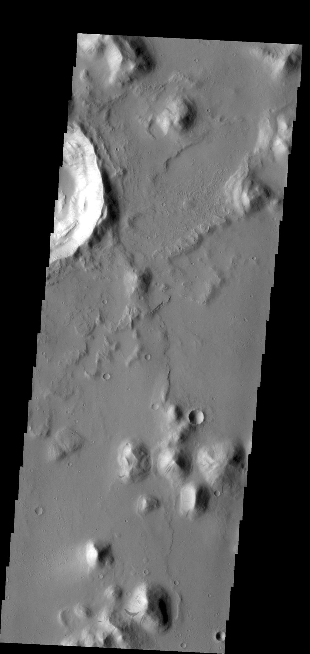The small hill in this image aptured by NASA's 2001 Mars Odyssey spacecraft of Amazonis Planitia has several dark slope streaks, believed to form when down slope movement of rocks or other debris clear off some of the dust cover.