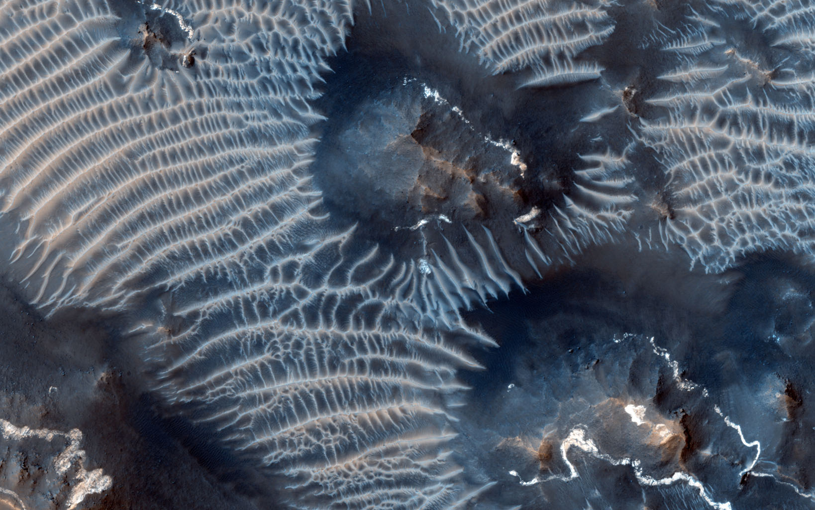 This colorful scene is situated in the Noctis Labyrinthus, perched high on the Tharsis rise in the upper reaches of the Valles Marineris canyon system as seen by NASA's Mars Reconnaissance Orbiter.
