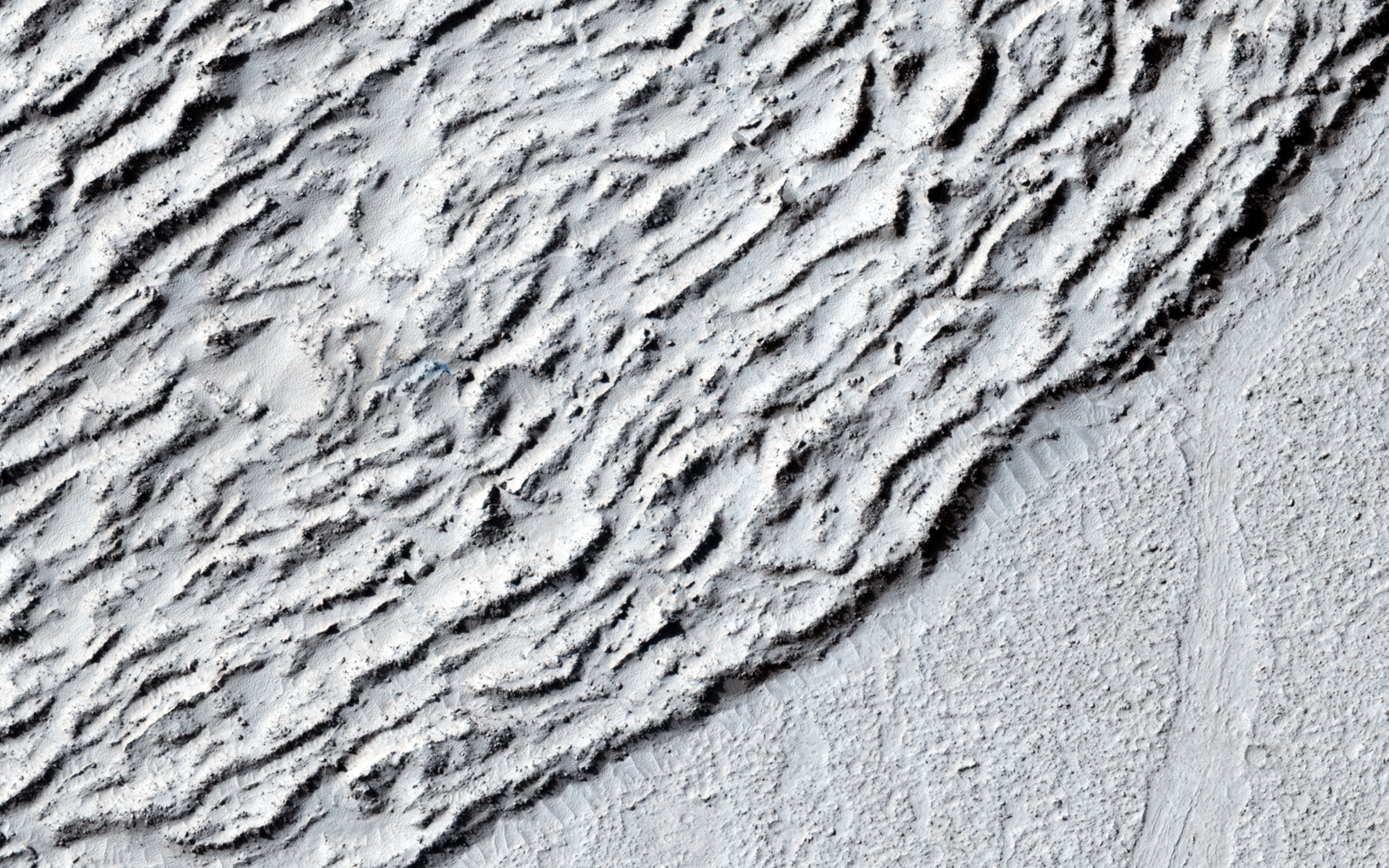 This image shows lava crumpled against the upstream side of an impact crater as seen by NASA's Mars Reconnaissance Orbiter.
