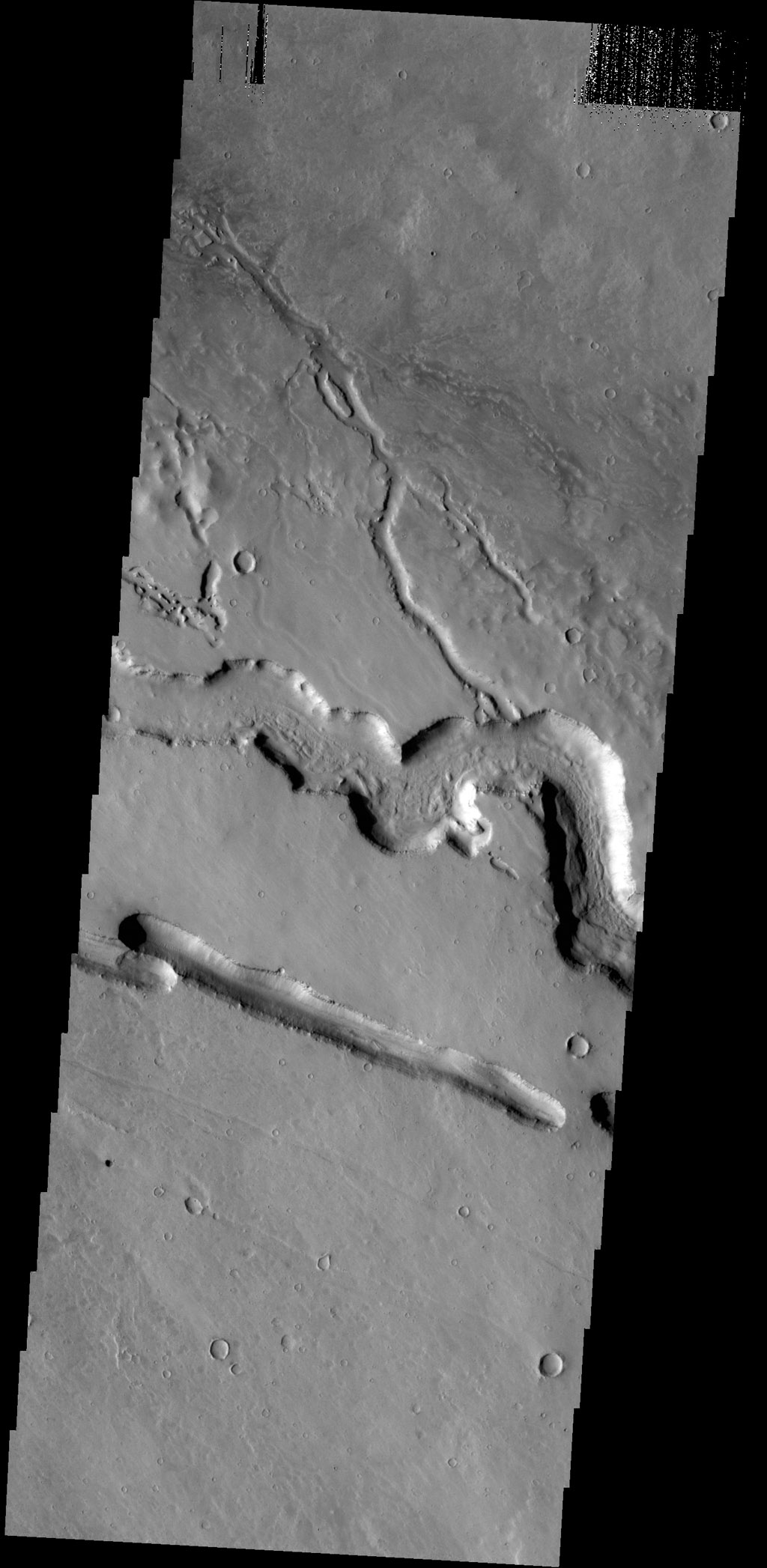 The channels and linear depression in this image captured by NASA's 2001 Mars Odyssey spacecraft are located on the western margin of the Elysium Volcanic complex. The channels were created by lava flow.