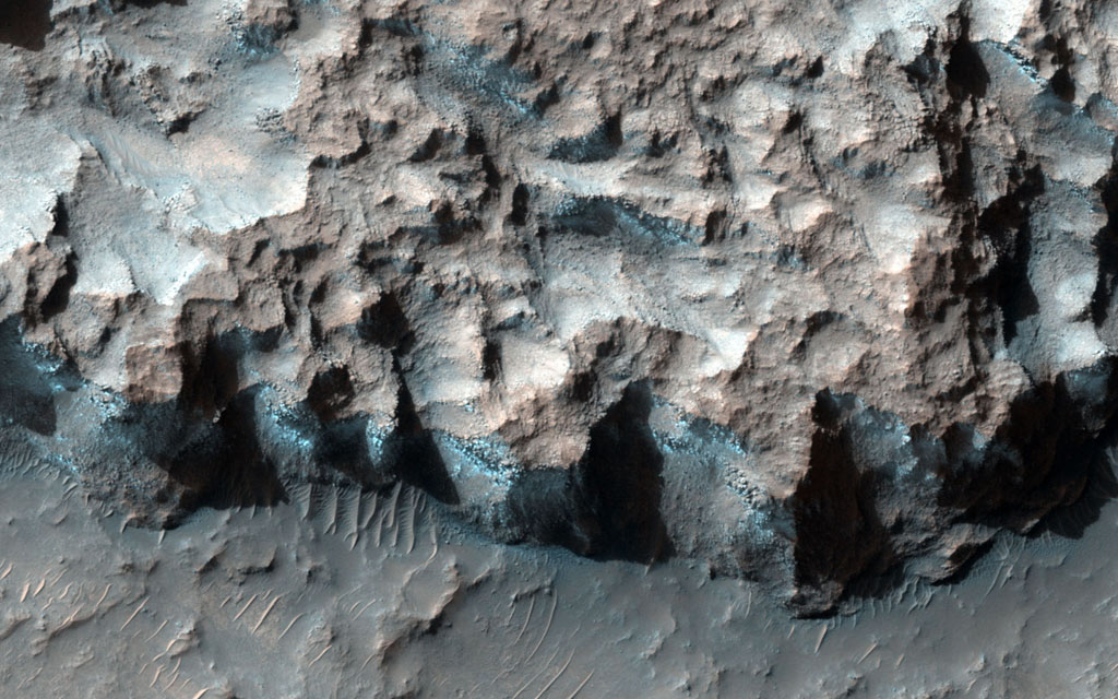 A south-facing escarpment in the Northwest Hellas region that was targeted for the phyllosilicates shows instances of bluish rock in this enhanced color image taken by NASA's Mars Reconnaissance Orbiter.