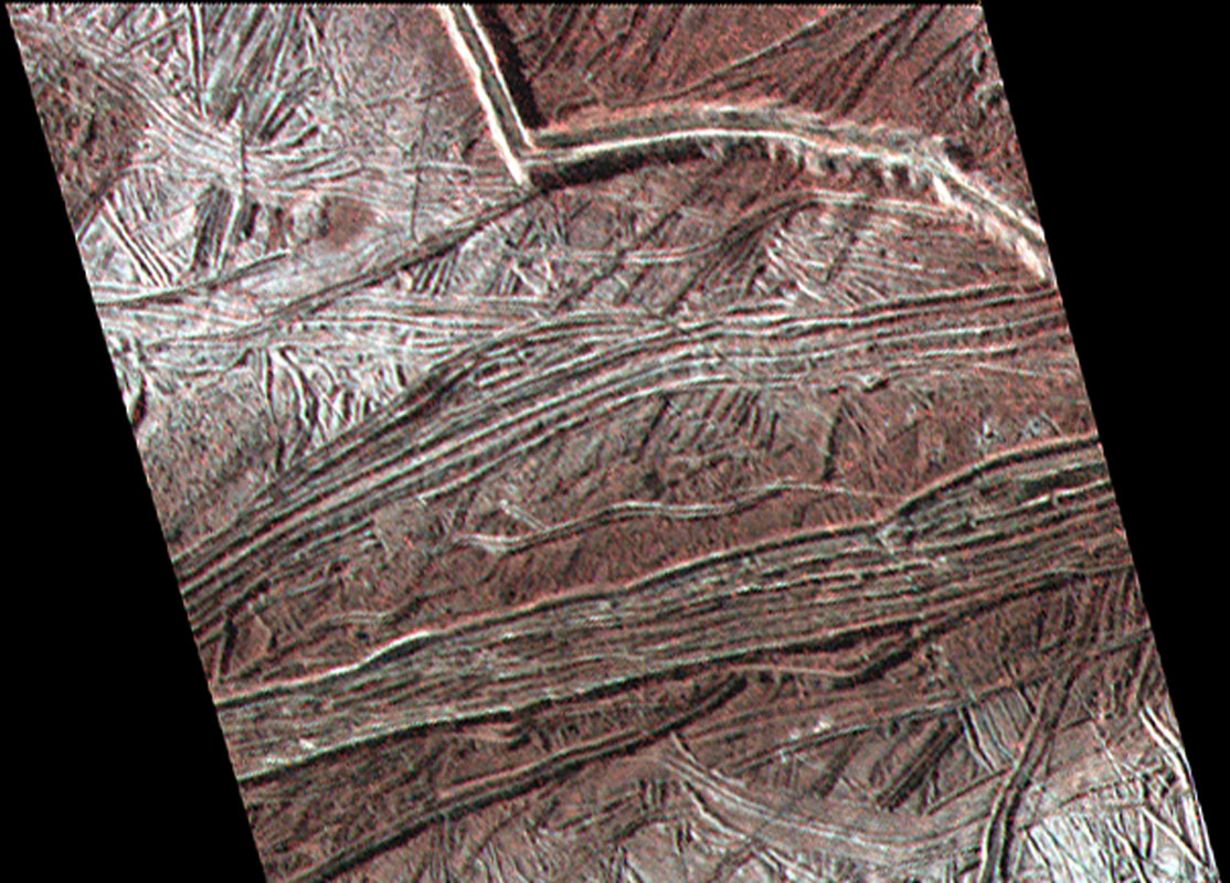 This enhanced color image shows cracks and ridges on Europa's surface that reveal a detailed geologic history. The view was captured by NASA's Galileo spacecraft on February 2, 1999.