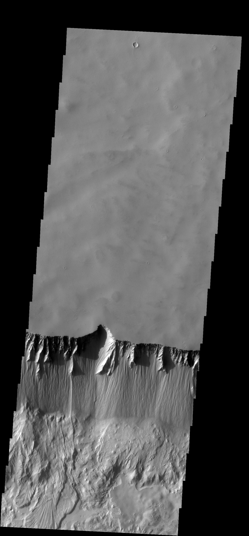 The steep northern wall of Tithonium Chasma crosses this image from NASA's 2001 Mars Odyssey spacecraft. Landslide deposits from slope failure can be seen at the lower left corner of the image.