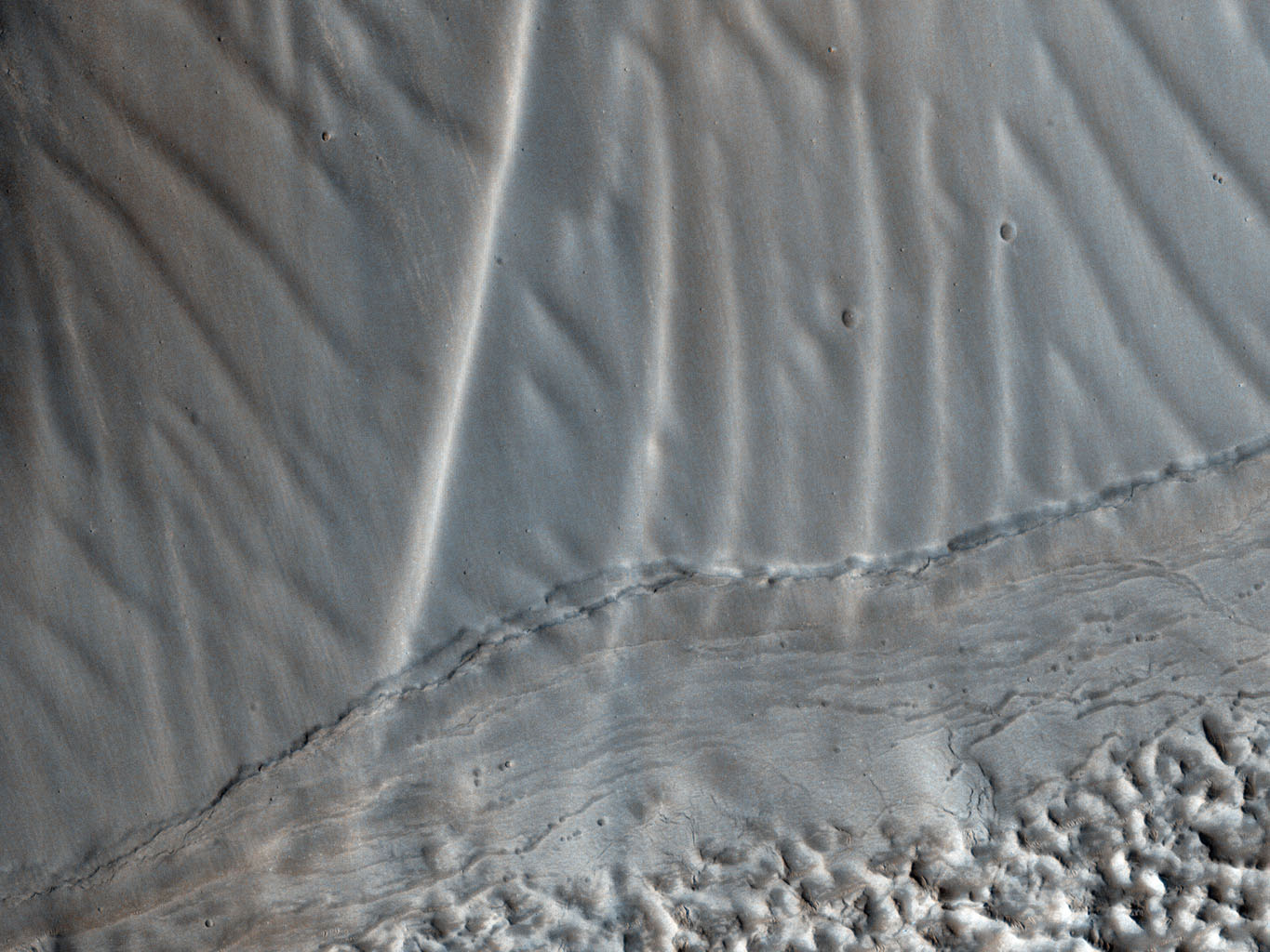 This observation from NASA's Mars Reconnaissance Orbiter shows a set of landforms that appears to form a nested 'chevron' pattern on a slope in Coloe Fossae. Interestingly, nearby surfaces on the same slope are all parallel.