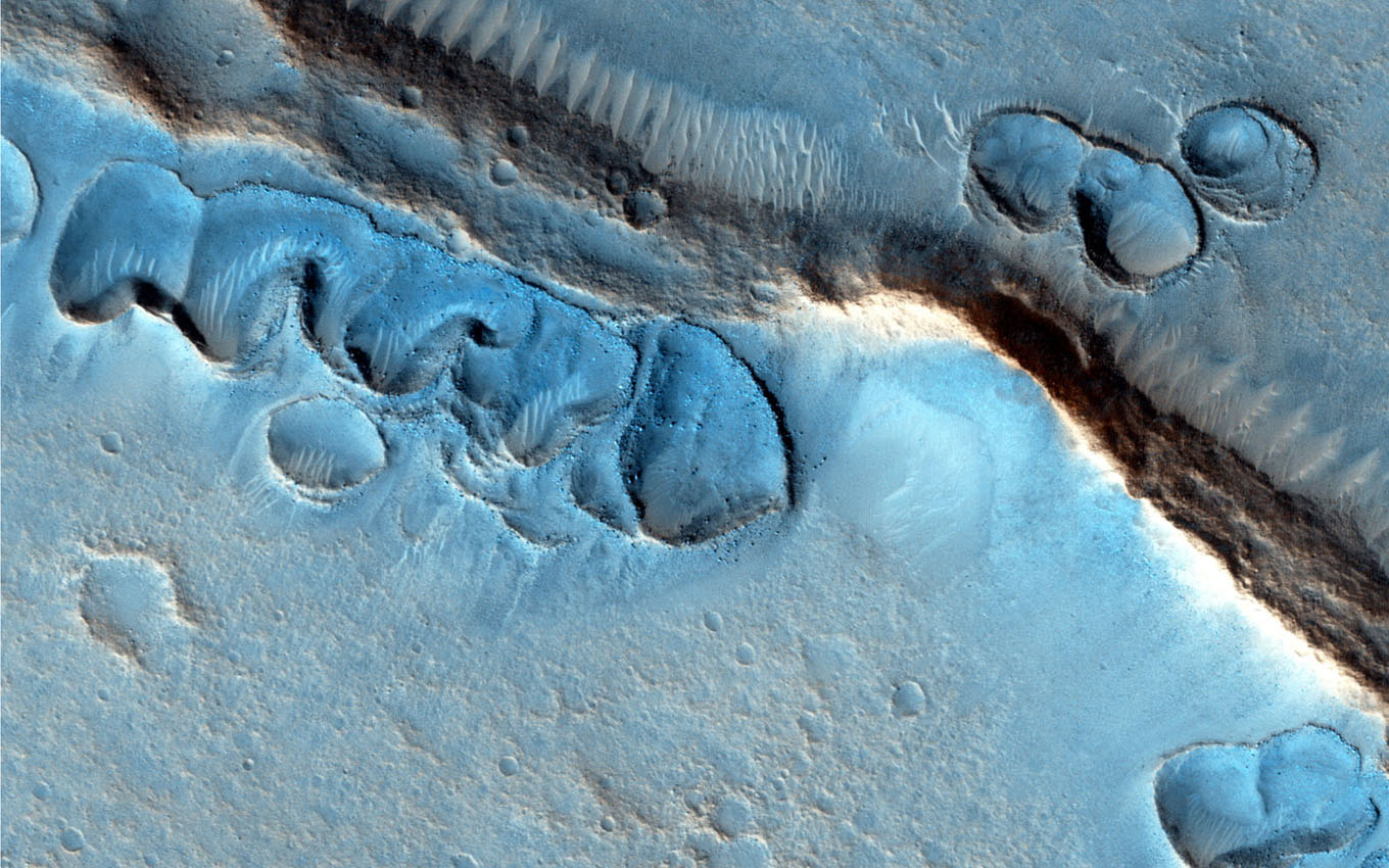 This image from NASA's Mars Reconnaissance Orbiter covers many shallow irregular pits with raised rims, concentrated along ridges and other topographic features.