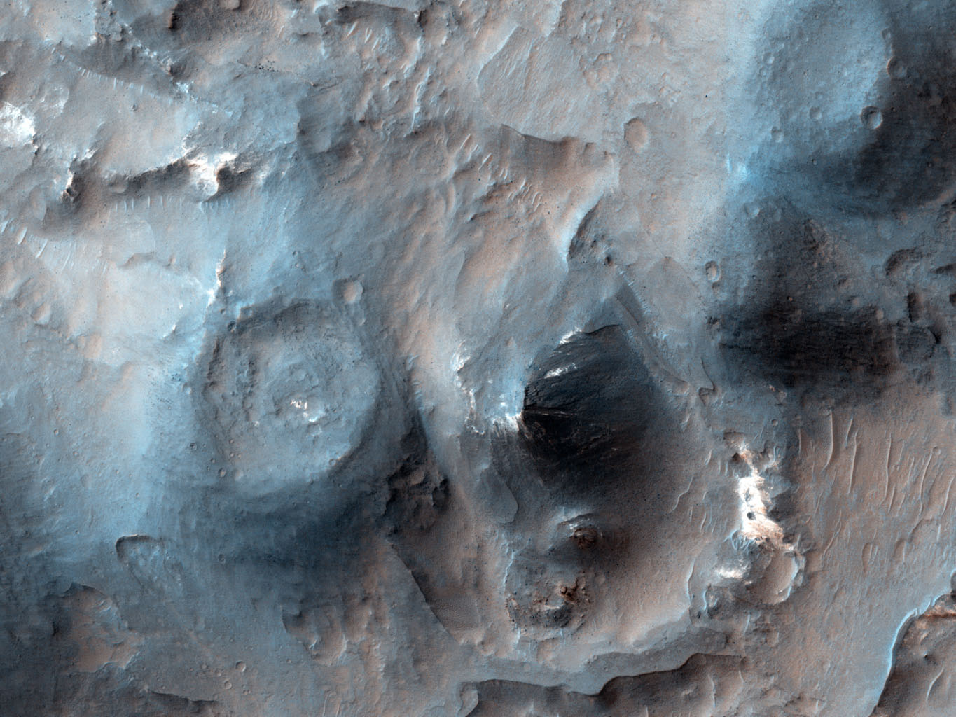 This image from NASA's Mars Reconnaissance Orbiter shows cones with summit pits that are very similar to cinder cones on Earth. They are also very well-preserved, peppered by only small impact craters, so they must be geologically young.