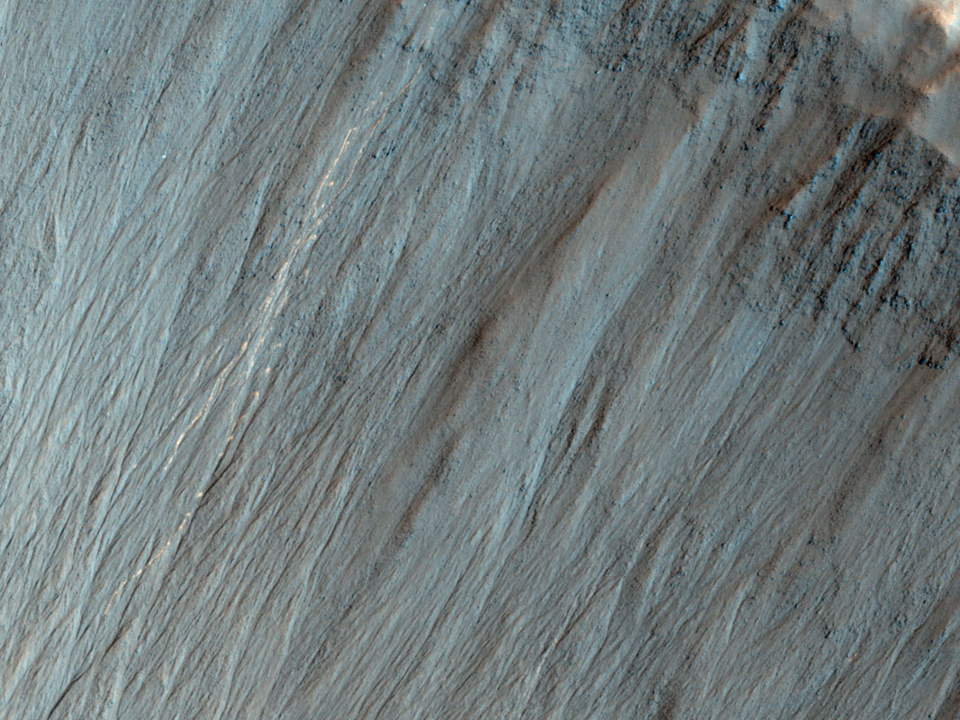 This image from NASA's Mars Reconnaissance Orbiter shows a well-preserved impact crater. A closeup view highlights distinctive bright lines and spots on the steep slope on the north side.