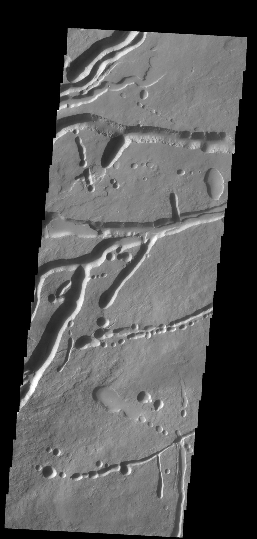 The pits, fractures and channel-like features captured by NASA's 2001 Mars Odyssey spacecraft are located on the northern flank of Ascraeus Mons. Most of these features were created by collapse into lava tubes that existed below the surface.