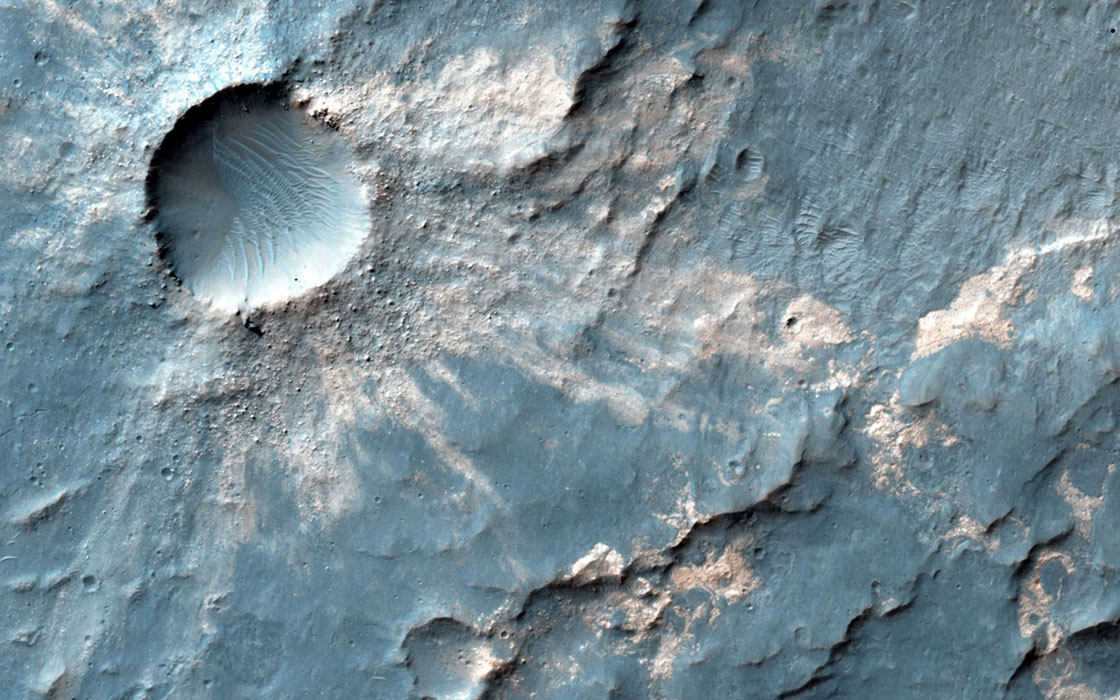 Sandwiched between a crater nearly 4 kilometer across and a much larger and older crater over 15-kilometers in diameter is this small impact crater with light-toned material exposed in its ejecta. This image is from NASA's Mars Reconnaissance Orbiter.