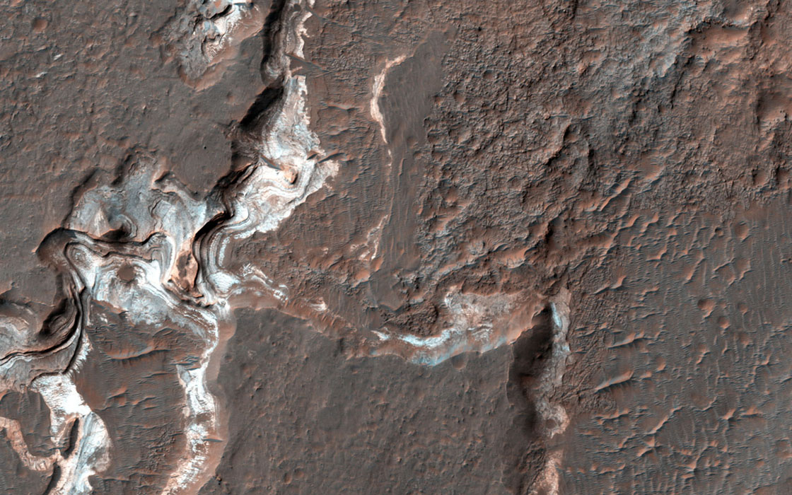 This image shows some bright layered deposits exposed within a linear trough along the floor of the Ladon Basin as seen by NASA's Mars Reconnaissance Orbiter.
