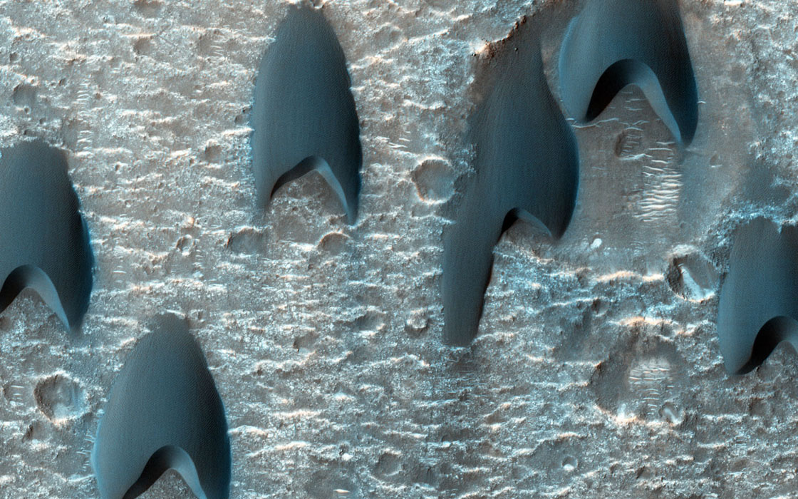 This image from NASA's Mars Reconnaissance Orbiter shows a dune field in a large crater near Mawrth Vallis; some of the dunes appear to be in 'V' formation.
