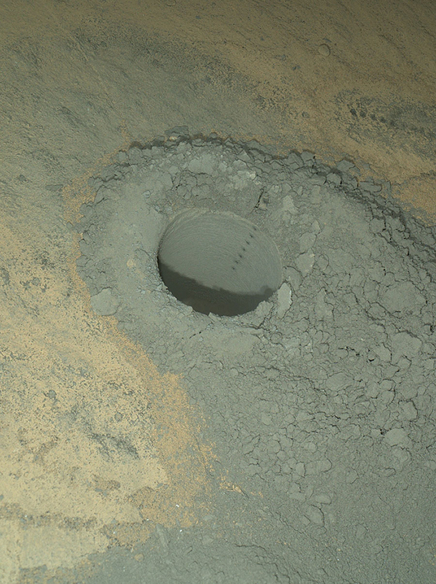 NASA's Curiosity Mars rover provided this nighttime view of a hole produced by the rover's drill and, inside the hole, a line of scars produced by the rover's rock-zapping laser.