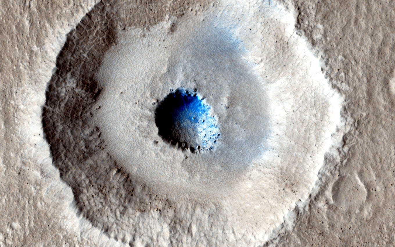 The crater in the center of this HiRISE image from NASA's Mars Reconnaissance Orbiter is unusual because there is a wide, flat bench, or terrace, between the outer rim and the inner section, making it appear somewhat like a bullseye.