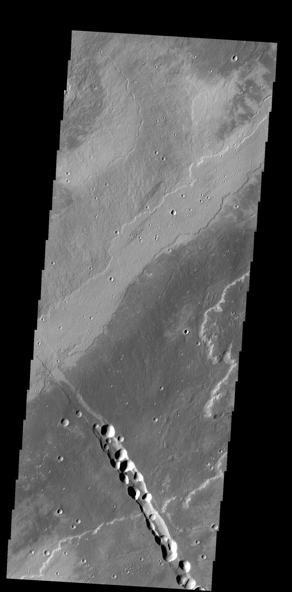 This image from NASA's 2001 Mars Odyssey spacecraft shows a small portion of the lava flows from Alba Mons. The depression and collapse features within it are part of the large system of tectonic features created by the apparent collapse of the volcano.