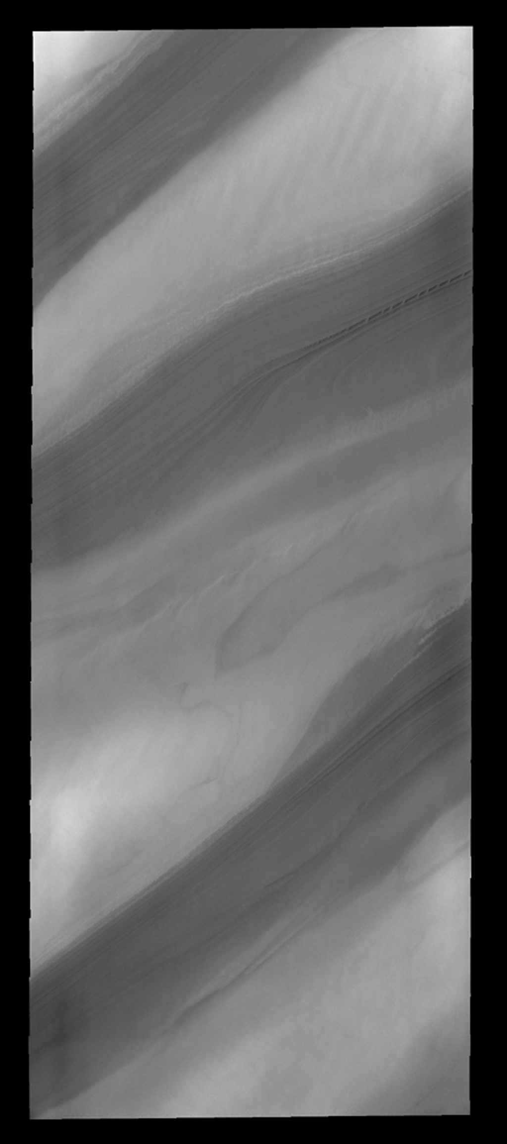 With summer fast approaching, the frost has sublimated away and the layers that make up the north polar cap are easily discernable, as seen by NASA's 2001 Mars Odyssey spacecraft.
