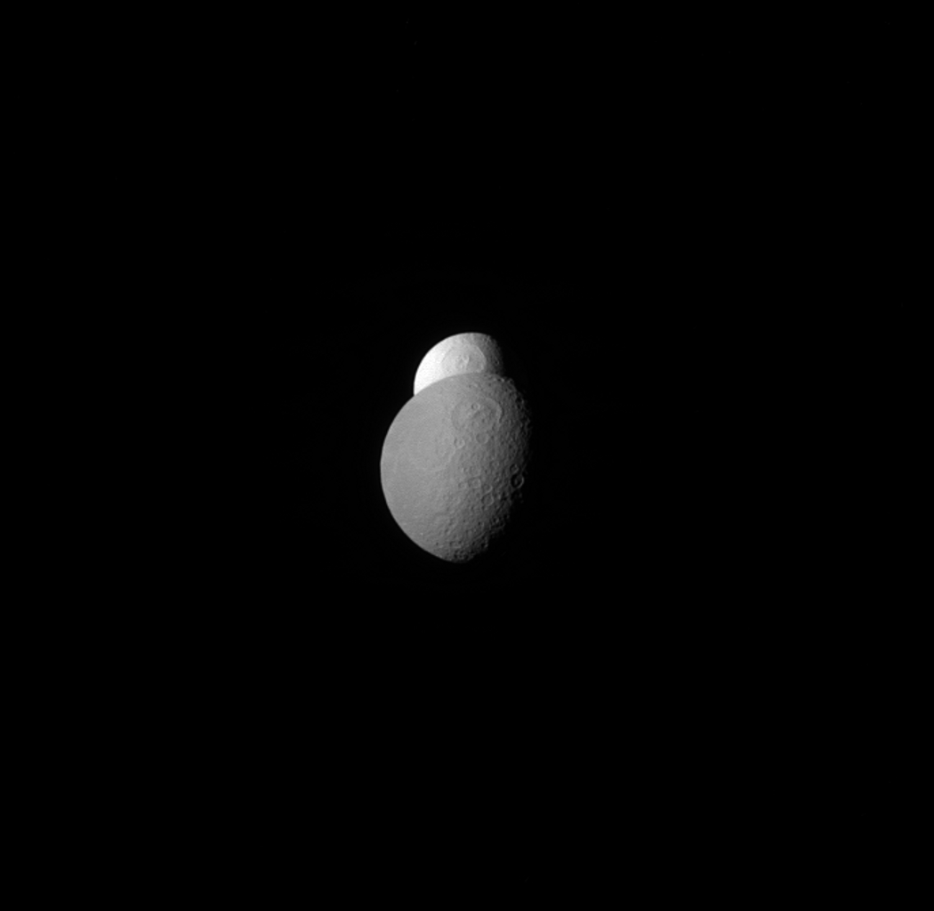 NASA's Cassini orbiter shows that Tethys appears to be peeking out from behind Rhea, watching the watcher. Scientists believe that Tethys' surprisingly high albedo is due to the water ice jets emerging from its neighbor, Enceladus.