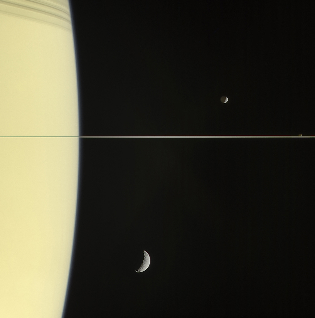 On March 13, 2006 Cassini's narrow-angle camera captured this look at Saturn and its rings, seen here nearly edge on. The frame also features Mimas and tiny Janus (above the rings), and Tethys (below the rings).