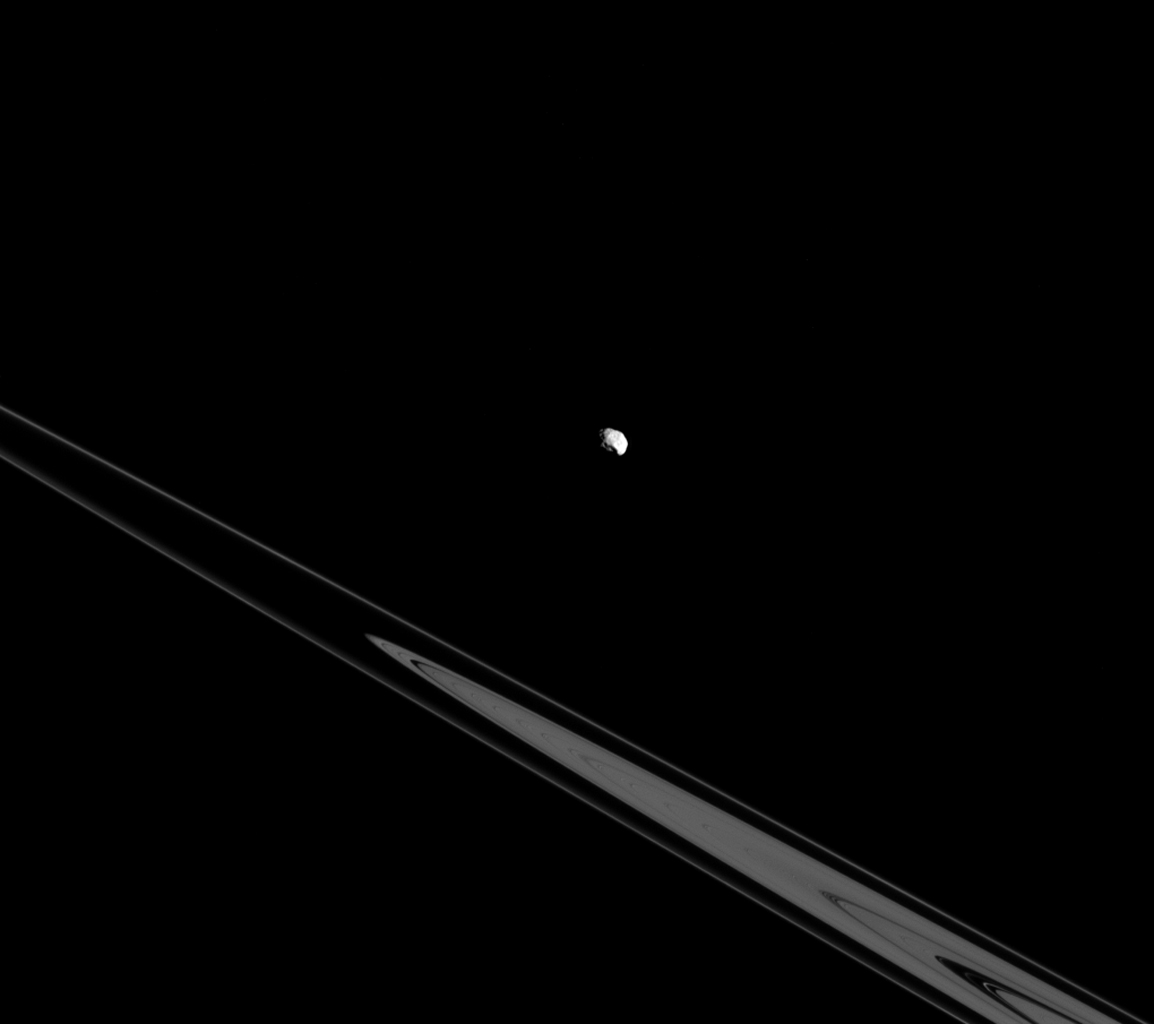 Although Epimetheus appears to be lurking above the rings here, it's actually just an illusion resulting from the viewing angle of NASA's Cassini spacecraft. In reality, Epimetheus and the rings both orbit in Saturn's equatorial plane.