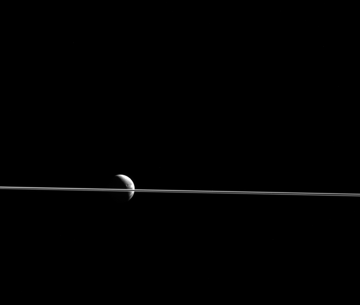 Dione appears cut in two by Saturn's razor-thin rings, seen nearly edge-on in a view from NASA's Cassini spacecraft.