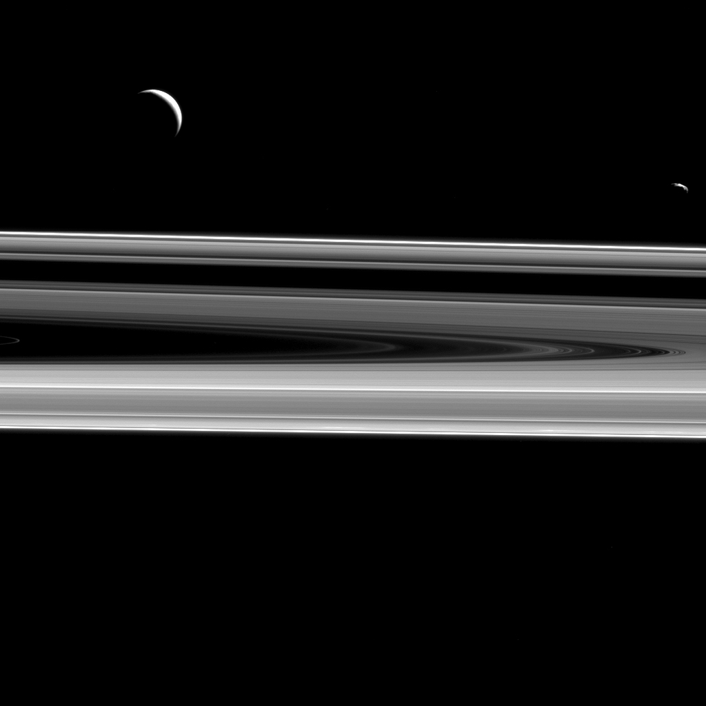 Two moons hover above the rings from this perspective, Enceladus (313 miles or 504 kilometers across), at left, and Janus (111 miles or 179 kilometers across), at right as seen by NASA's Cassini spacecraft.