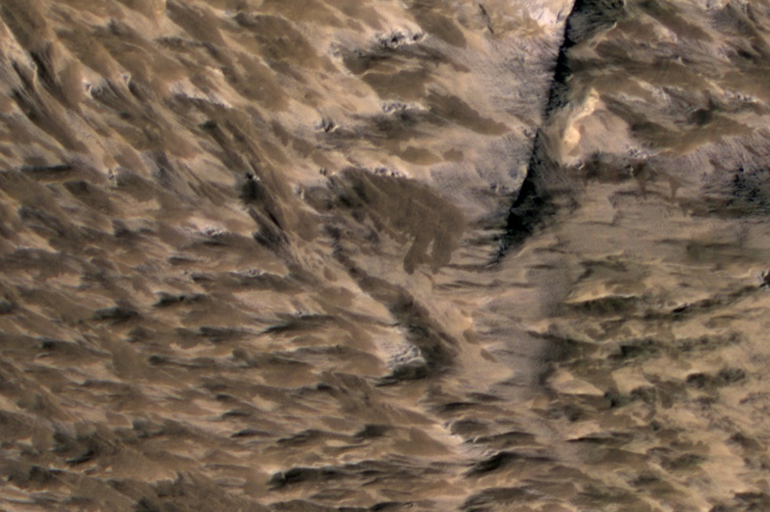 This April 6, 2014, image from NASA's Mars Reconnaissance Orbiter shows numerous landslides in the vicinity of where an impact crater was excavated in March 2012.
