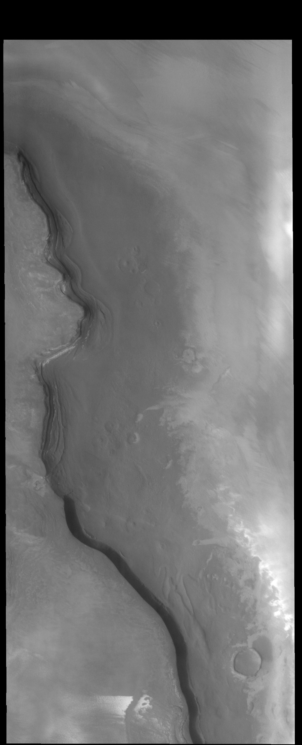 The cliff face in this image captured by NASA's 2001 Mars Odyssey spacecraft is called Rupes Tenius (rupes = scarp). The polar cap is the higher region to the left and the plains are located on the right side of the image.