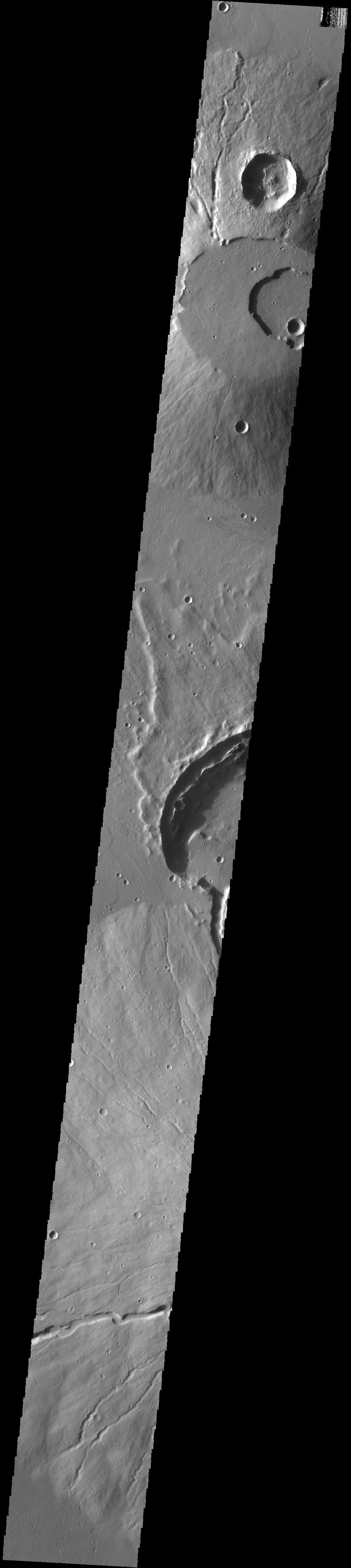 This image captured by NASA's 2001 Mars Odyssey spacecraft crosses the summit of Uranius Tholus, as well as the western flank of Ceraunius Tholus.