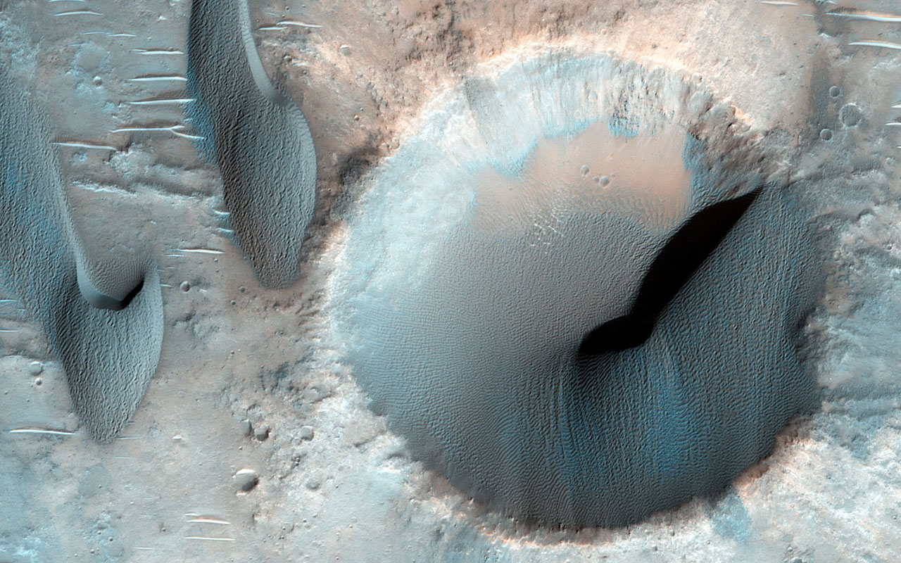 This image NASA's Mars Reconnaissance Orbiter shows dozens of dark-toned dunes in and around several craters within the rugged terrain of Terra Cimmeria.