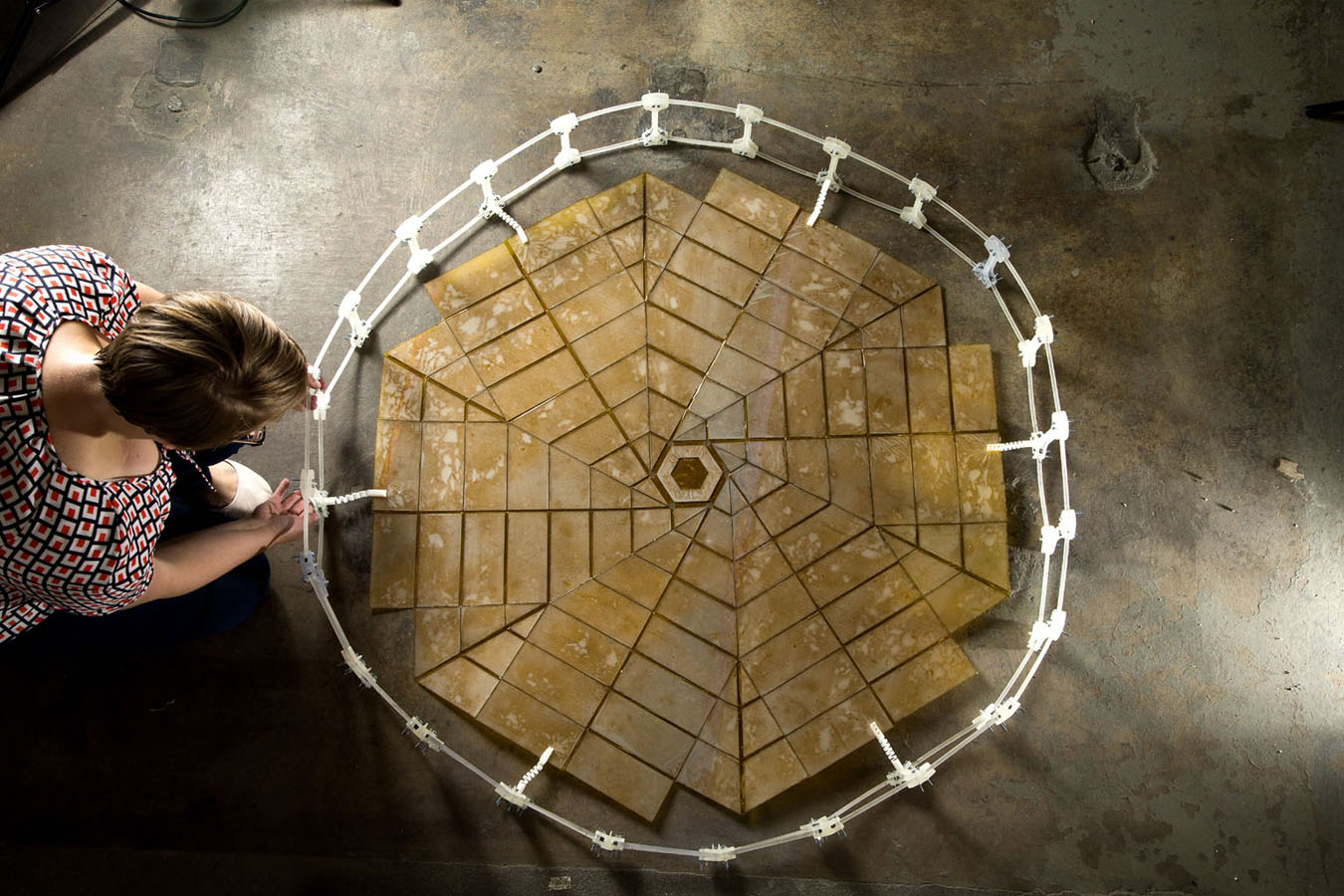 A Ph.D. student in mechanical engineering at Brigham Young University, Provo, Utah, unfolds a solar panel array that was designed using the principles of origami.