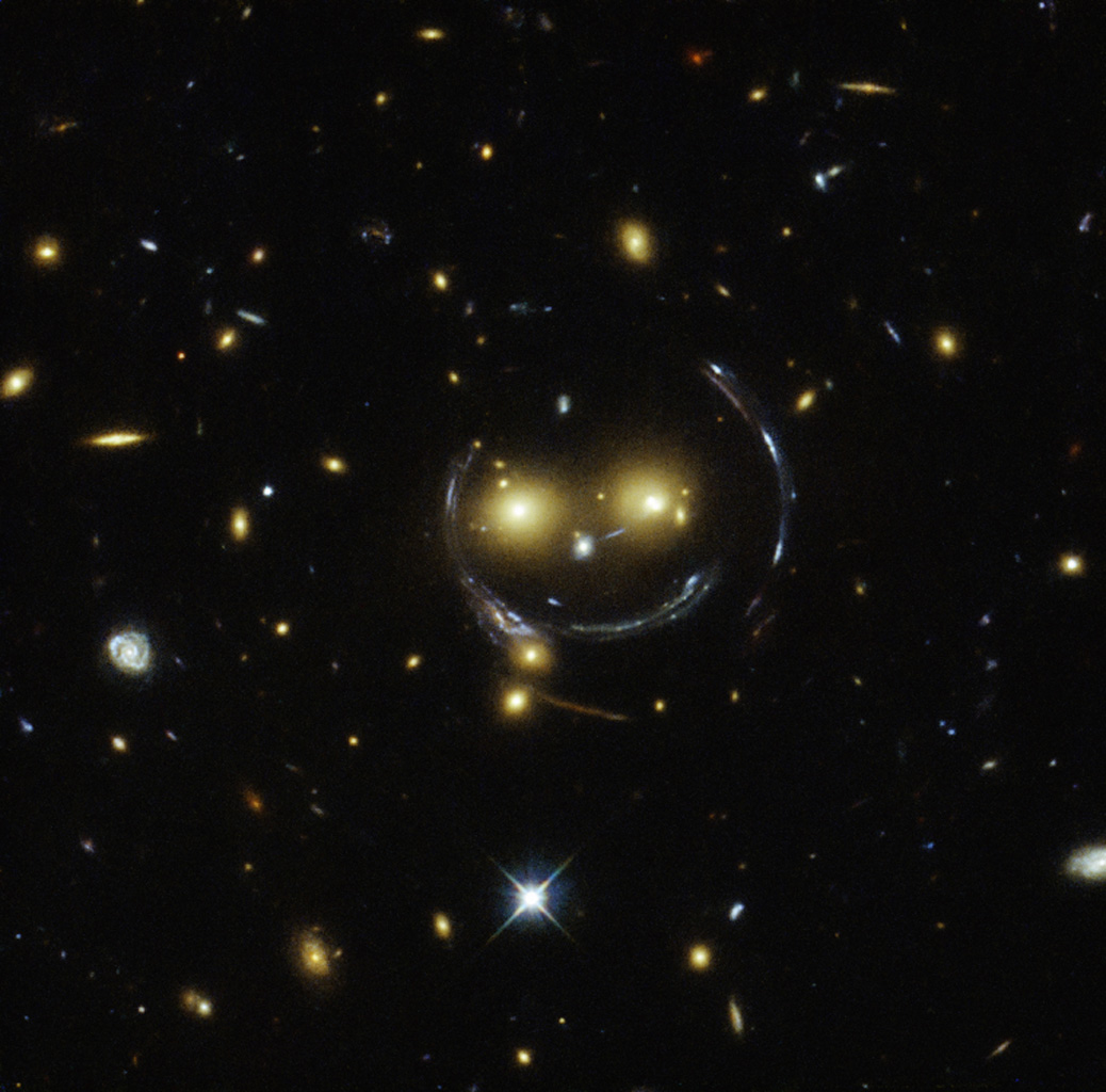 This image from the NASA/ESA Hubble Space Telescope shows a galaxy cluster, SDSS J1038+4849, that appears to have two eyes and a nose as part of a happy face. The 'face' is the result of gravitational lensing.