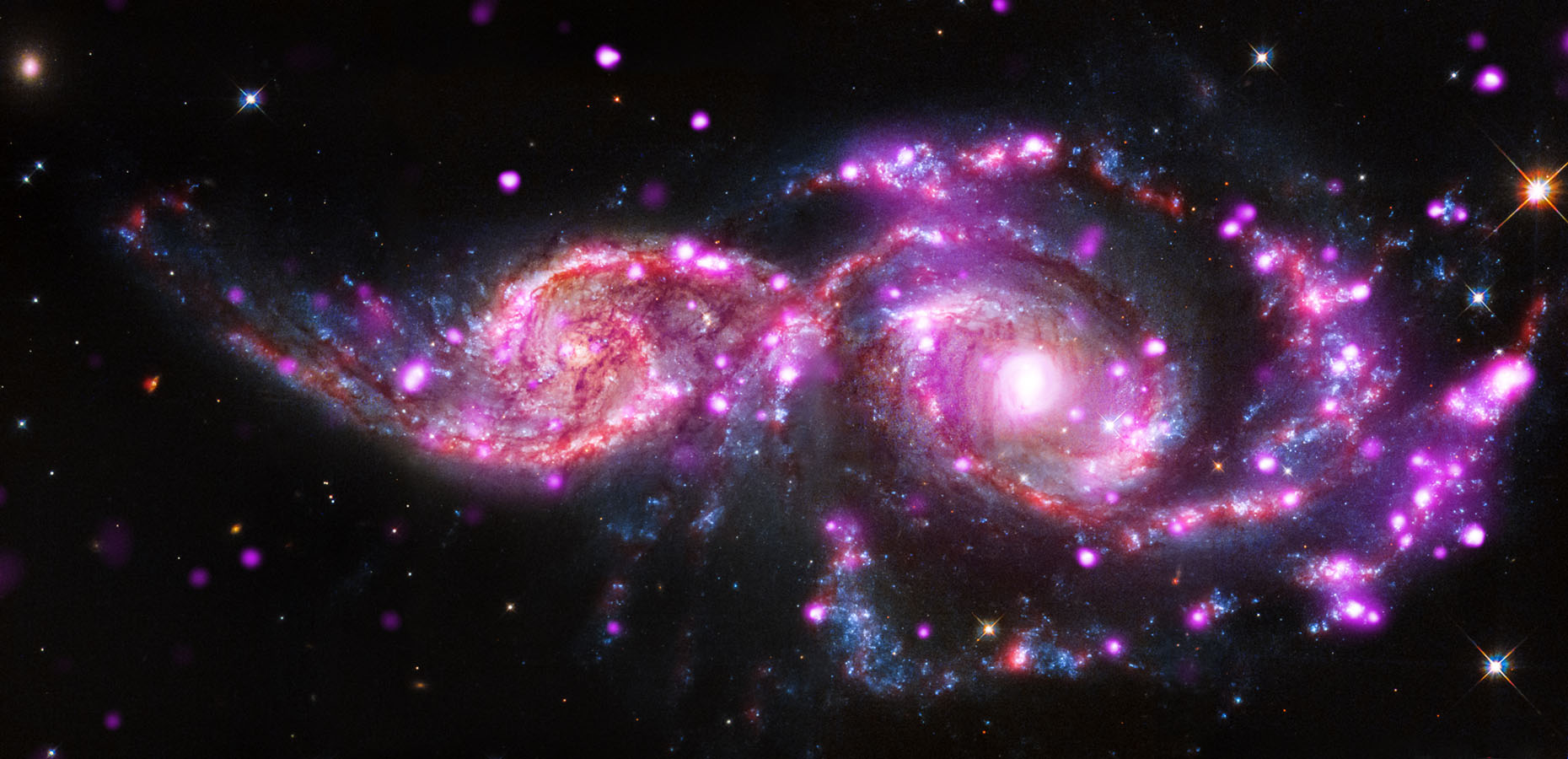 This composite image of NGC 2207 and IC 2163 contains data from Chandra, NASA's Hubble Space Telescope and the Spitzer Space Telescope.