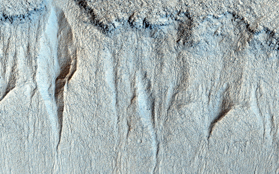 NASA's Mars Reconnaissance Orbiter observes a group of small gullies along a rock layer on the south wall of Liu Hsin Crater. At the foot of the gullies 'fans' of granular sediment have been deposited downhill from the gully formation.