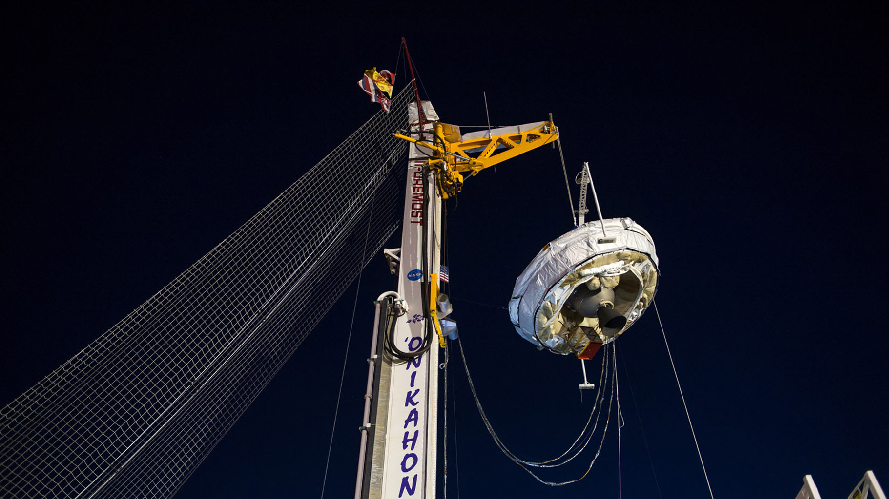 NASA's Low-Density Supersonic Decelerator hangs from a launch tower at U.S. Navy's Pacific Missile Range Facility in Kauai, Hawaii. The saucer-shaped vehicle will test two devices for landing heavy payloads on Mars.